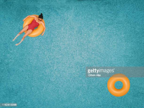 carefree woman on ring in swimming pool - rubber ring stock pictures, royalty-free photos & images