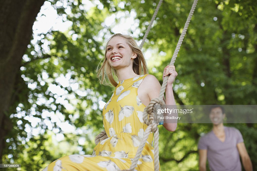 Carefree woman on swing under trees : Stock Photo