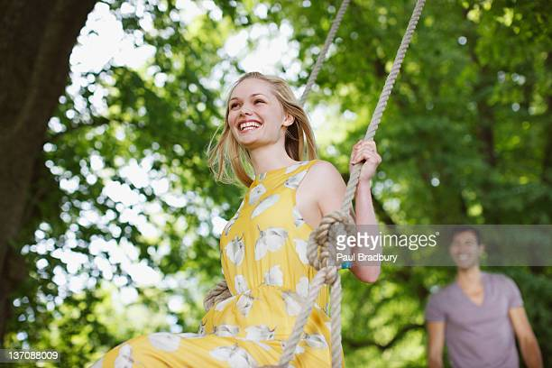 Carefree woman on swing under trees