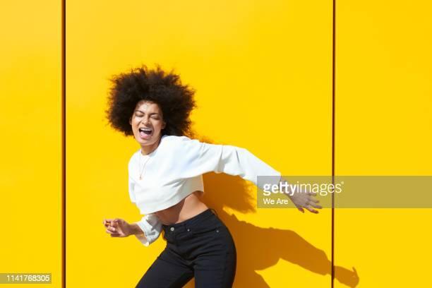 carefree woman radiating sunshine - モノトーンファッション ストックフォトと画像