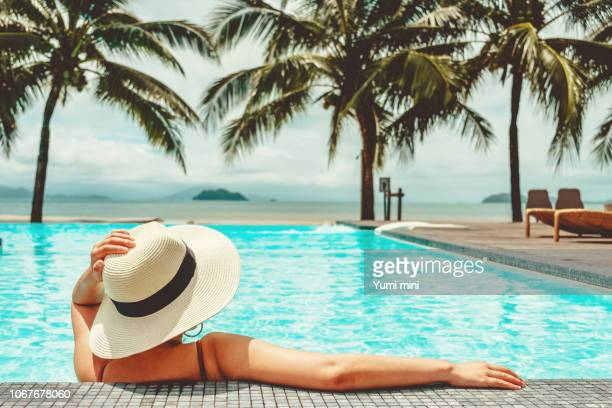 carefree woman relaxation in swimming pool summer holiday concept - tourist resort stock pictures, royalty-free photos & images