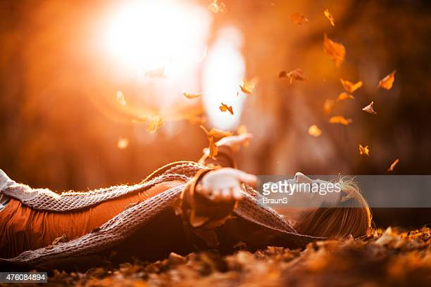 Carefree woman relaxing and throwing autumn leaves in nature.