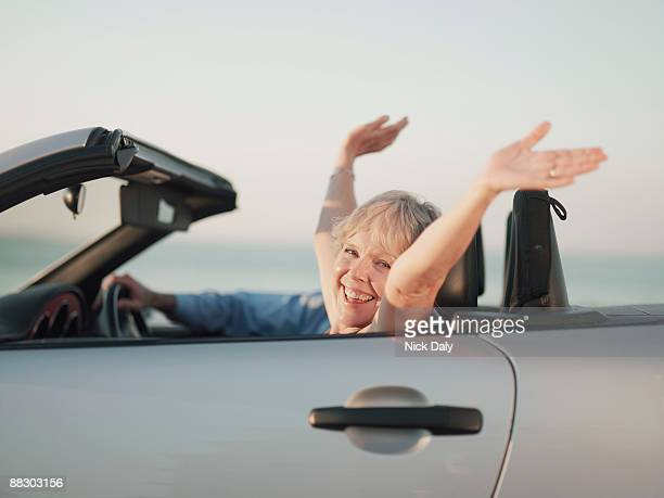 Carefree woman riding in convertible car