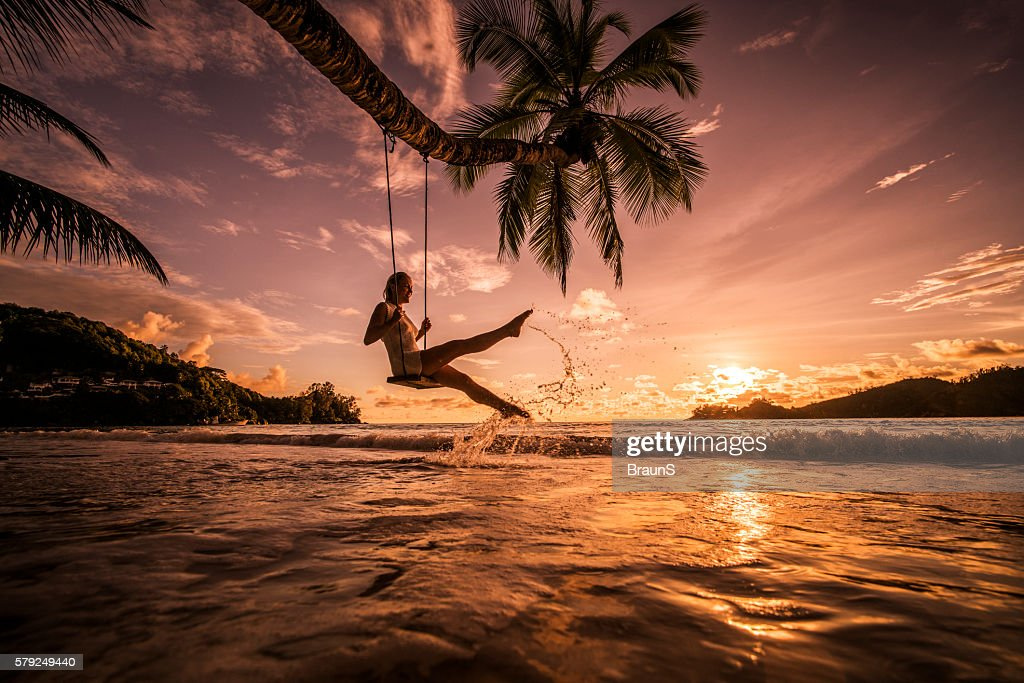 Carefree woman swinging above the sea at sunset beach. : Stock Photo