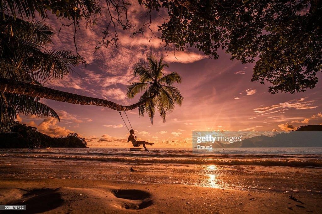 Entspannte Frau schwingen über dem Meer ein Sonnenuntergang Strand. : Stock-Foto