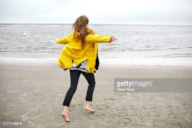 carefree woman wearing raincoat running on the beach - gelb stock-fotos und bilder