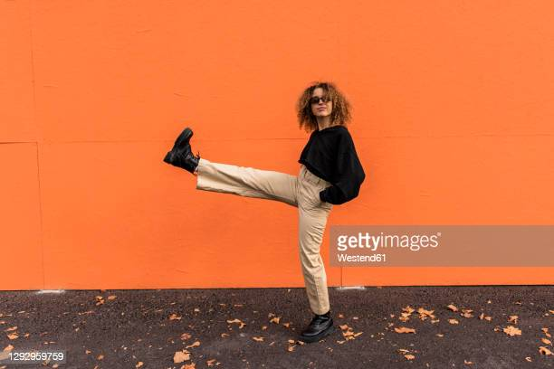 carefree woman wearing sunglasses stretching leg while standing on footpath - cool attitude stock pictures, royalty-free photos & images