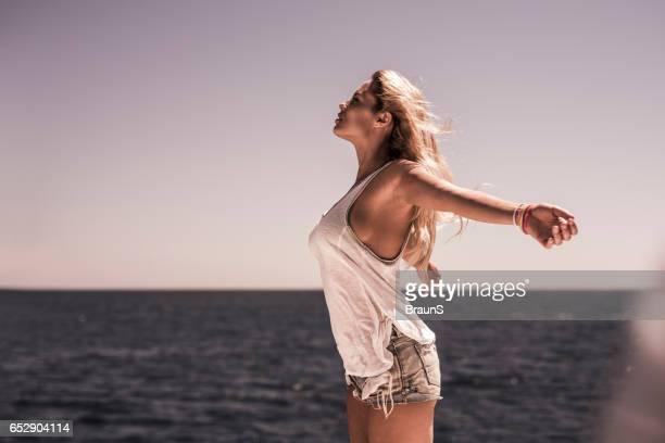 Mujer despreocupada con los brazos extendidos disfrutando en verano.
