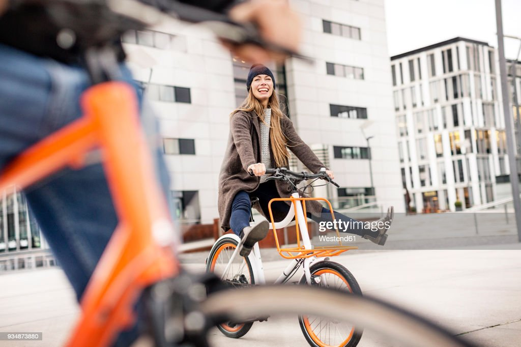 Carefree woman with man riding bicycle in the city : Photo