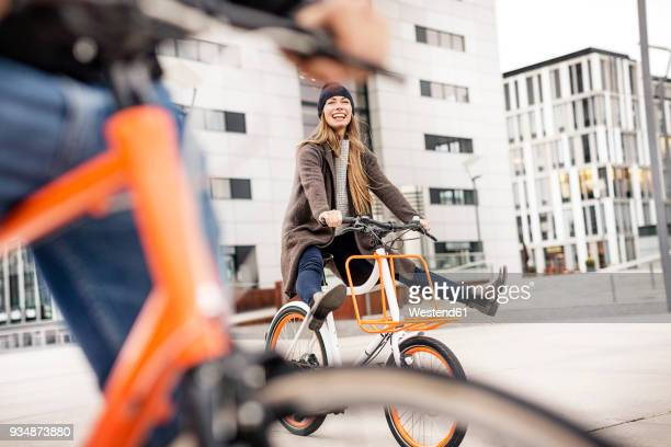 carefree woman with man riding bicycle in the city - radfahren stock-fotos und bilder