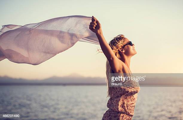 Carefree woman with shawl at sunset.