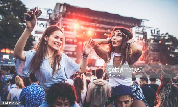 sorgfria kvinnor som har roligt under musik konsert med sina pojk vänner. - traditionell festival bildbanksfoton och bilder