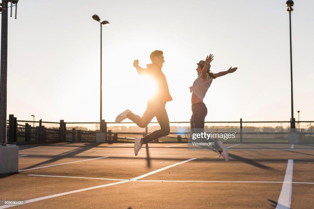 Carefree young couple jumping on parking levelat sunset : Stockfoto