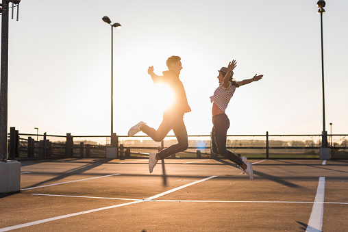 Carefree young couple jumping on parking levelat sunset - gettyimageskorea