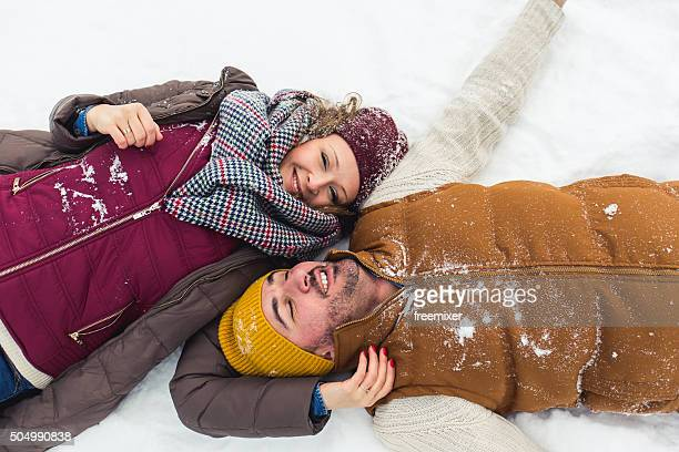 Carefree young couple playing with snow