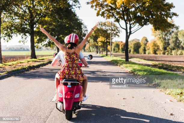 Carefree young couple riding motor scooter on country road