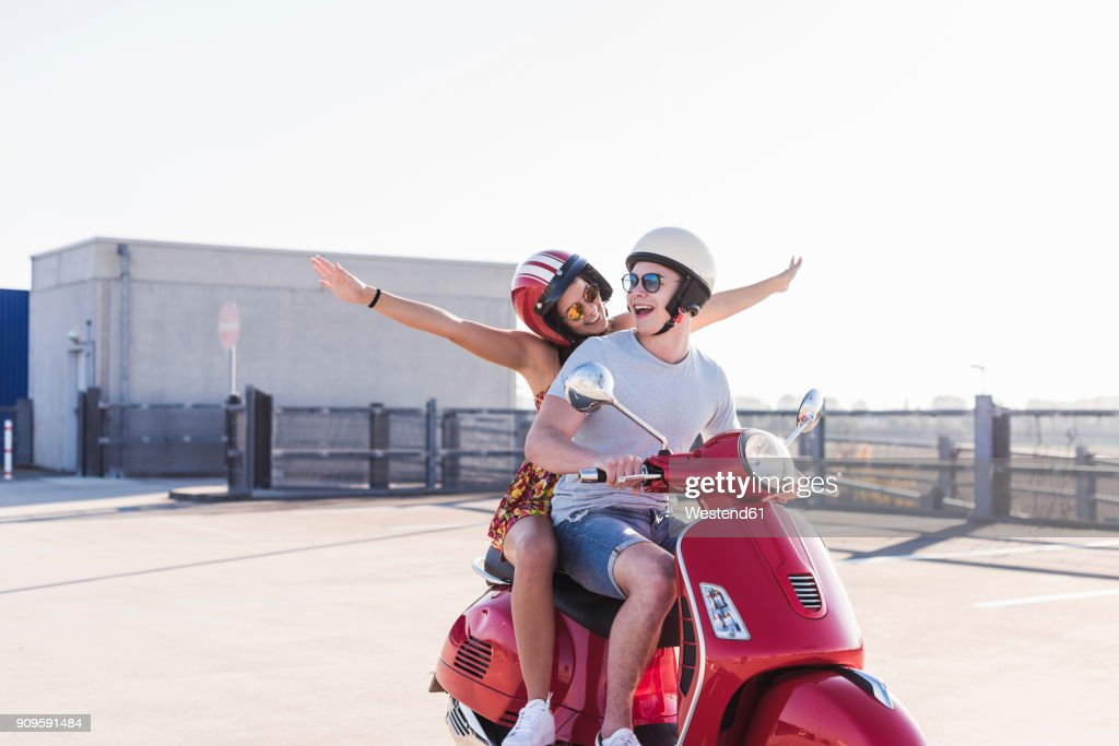 Carefree young couple riding motor scooter on parking level : Stock Photo