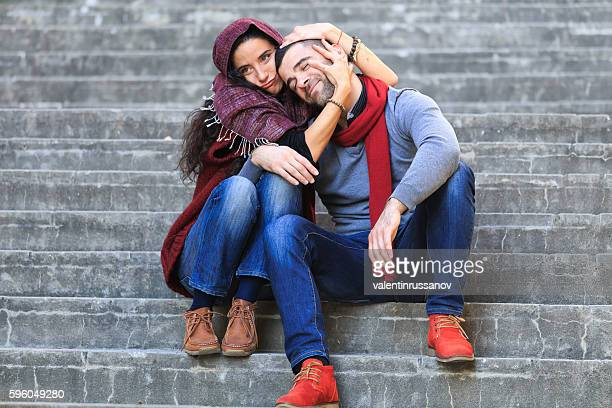 Carefree young couple sitting on stairs and having fun