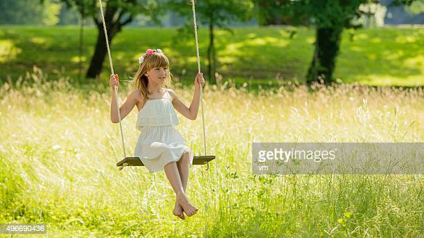 Carefree young girl swinging on park swing