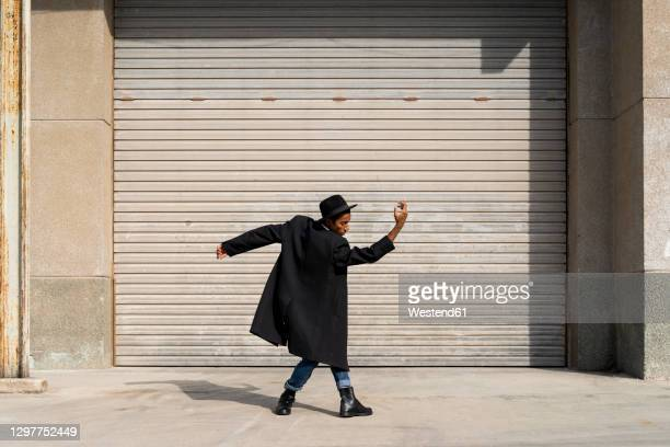 carefree young man enjoying day by dancing against shutter on sunny day - dancer stock pictures, royalty-free photos & images