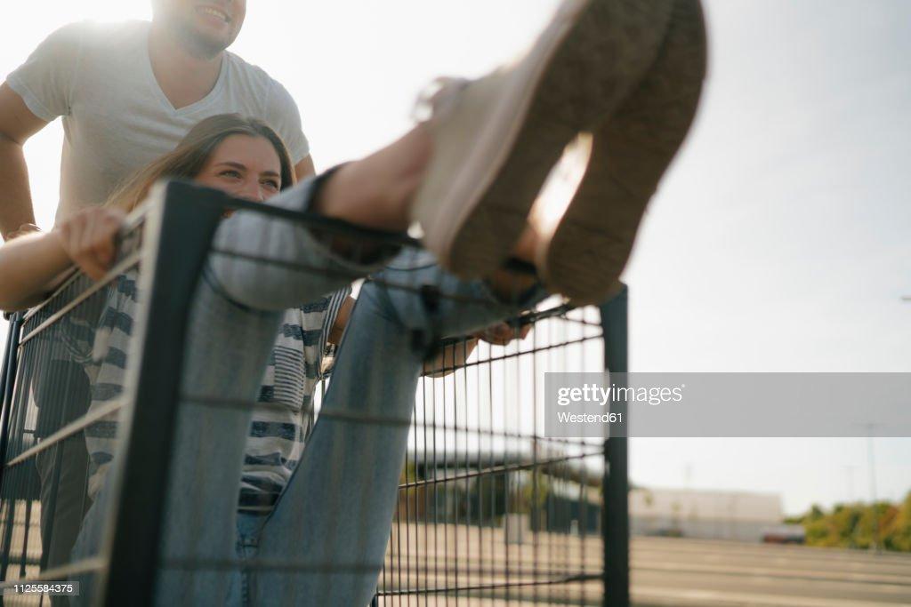 Carefree young man pushing girlfriend in a shopping cart : Stock-Foto