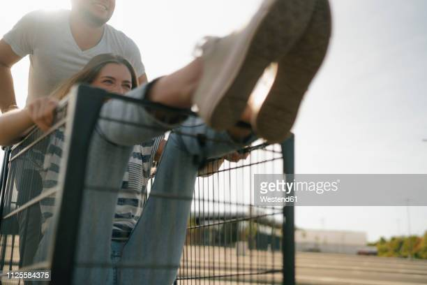 carefree young man pushing girlfriend in a shopping cart - carefree stock pictures, royalty-free photos & images