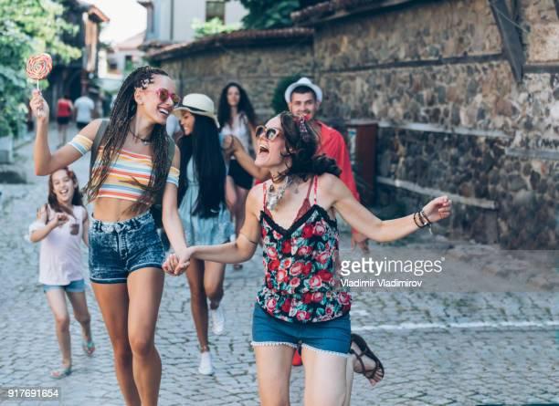 carefree jóvenes corriendo en la calle - pueblo fotografías e imágenes de stock