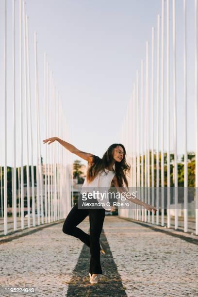 carefree young woman dancing in park - solo una donna giovane foto e immagini stock