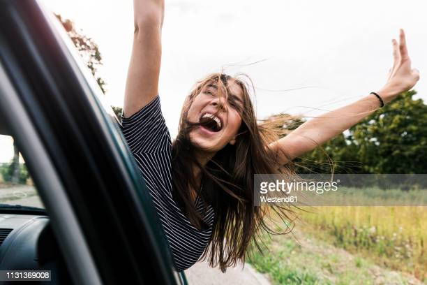 carefree young woman leaning out of car window screaming - libertad fotografías e imágenes de stock