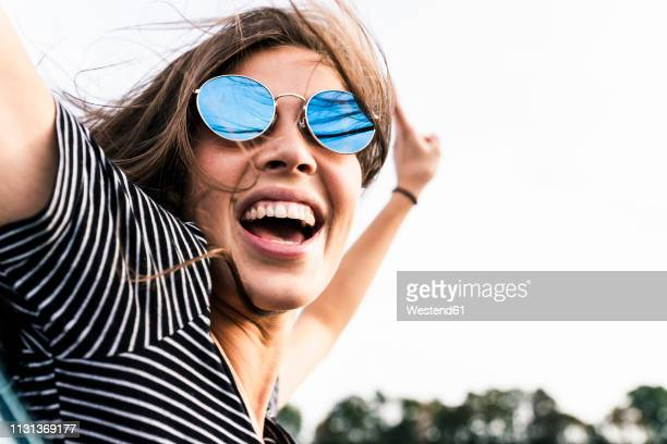 carefree young woman leaning out of car window screaming - opwinding stockfoto's en -beelden
