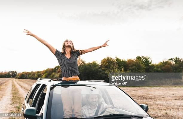 carefree young woman looking out of sunroof of a car - day 2 stock-fotos und bilder