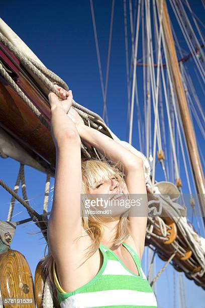Carefree young woman on a sailing ship