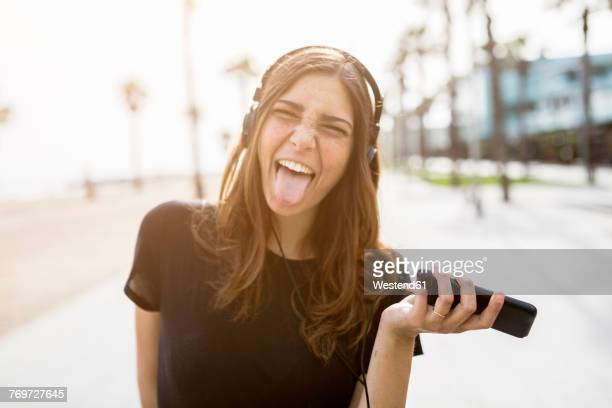 carefree young woman on boardwalk listening to music - tongue stock pictures, royalty-free photos & images