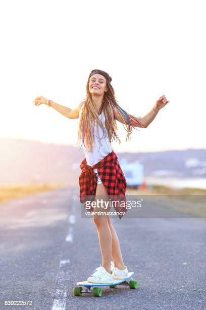 unbeschwerte junge frau skateboarden auf landstraße - longboard skating stock-fotos und bilder