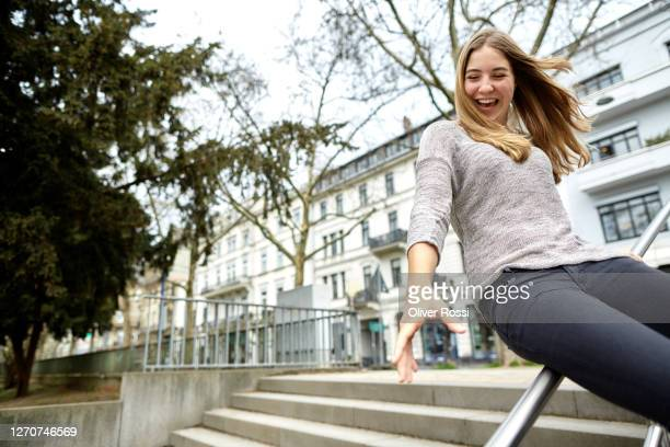 carefree young woman sliding on handrail in the city - railings stock pictures, royalty-free photos & images