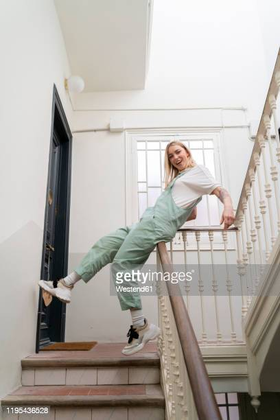 carefree young woman sliding on railing in staircase - sliding stock pictures, royalty-free photos & images