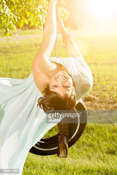 Carefree young woman swinging on a tire swing