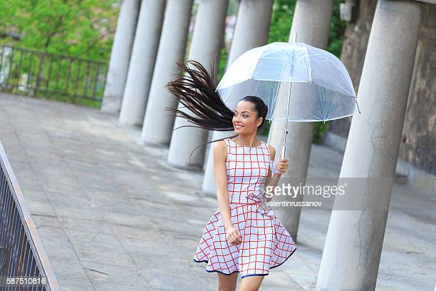 Carefree young woman walking under the rain