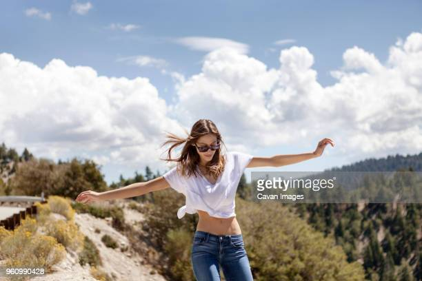 carefree young woman walking with arms outstretched on mountain against cloudy sky - クロップトップ ストックフォトと画像