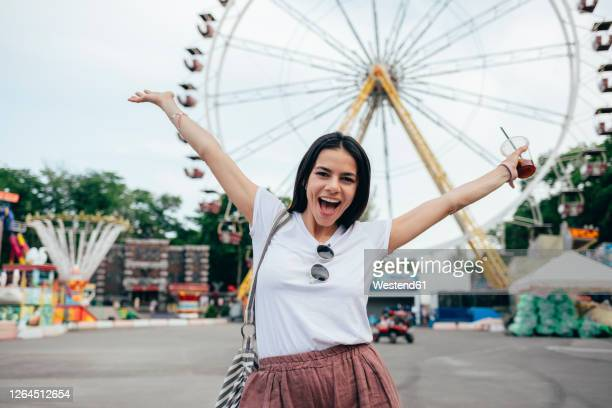 carefree young woman with arms raised standing at amusement park - ukraine stock pictures, royalty-free photos & images
