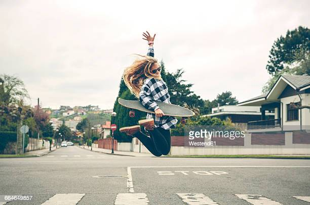 carefree young woman with skateboard jumping on the street - 25 29 anos imagens e fotografias de stock