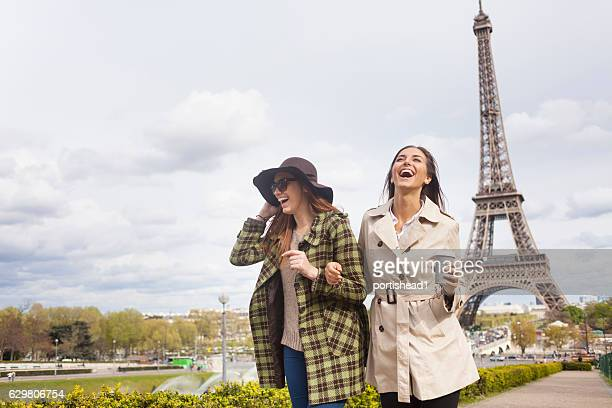 Carefree young women holding hands and having fun in Paris