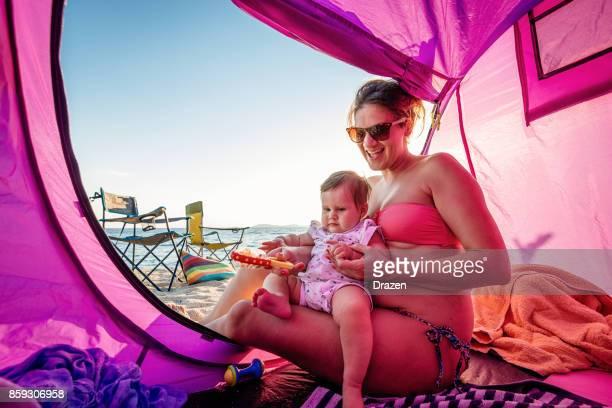Sorgfältige Mutter hält ihr Baby im Zelt am Strand