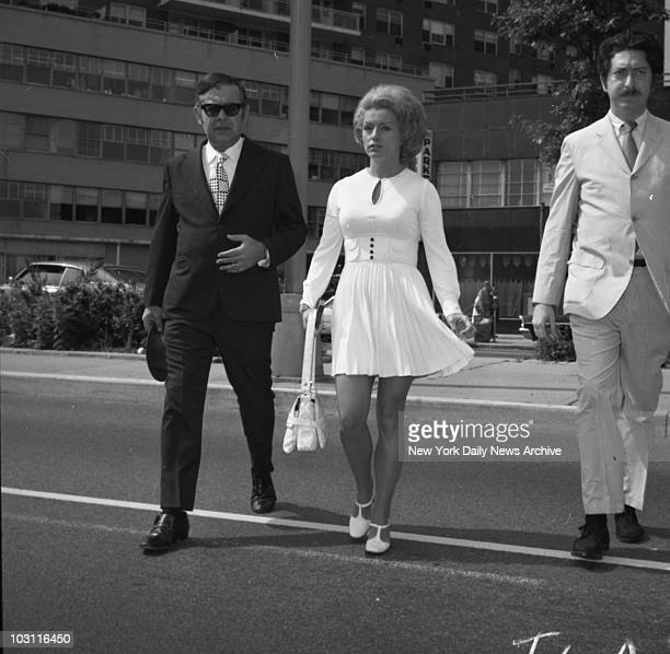 Carefully coiffed and very chic in a white outfit and accessories, Alice Crimmins strolls to Queens Supreme Court with her defense attorney, Herbert...