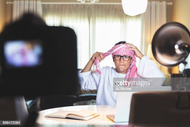 Carefully wearing a headscarf, to make a video to post online on social media