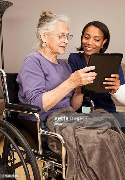 caregiver and elderly on digital tablet