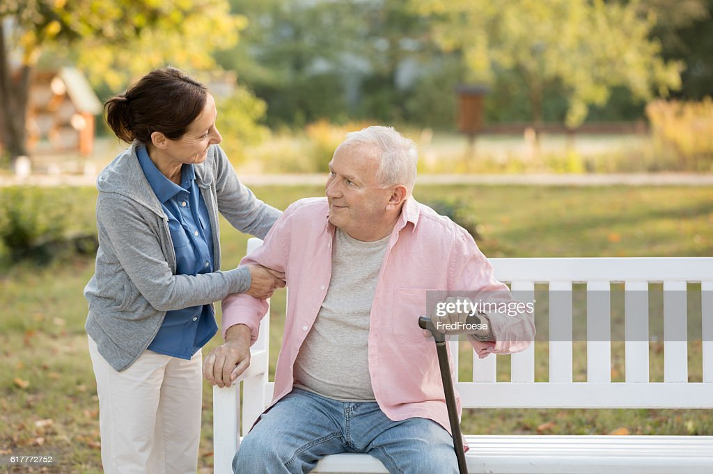 Caregiver and senior man in the park on park bench : Stock Photo