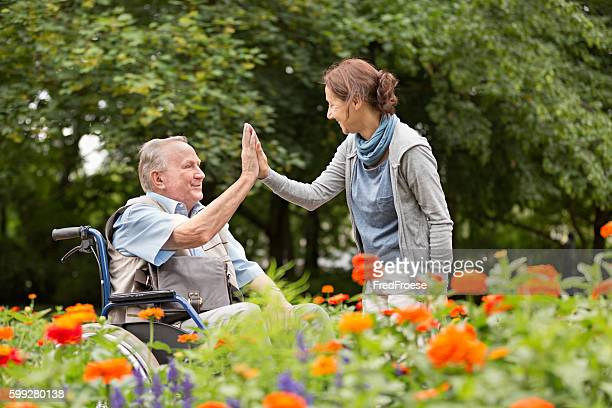 Caregiver and senior man on a wheelchair, walking in park