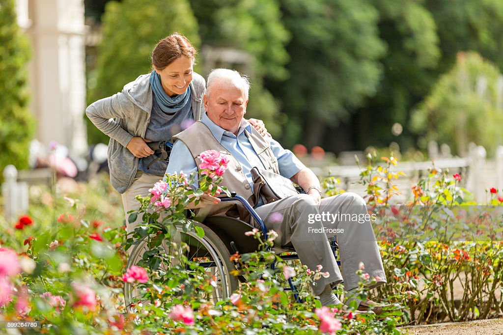 Caregiver and senior man on a wheelchair walking outdoors : Stock Photo