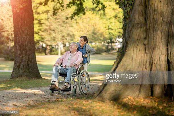 Caregiver and senior man on a wheelchair walking outdoors